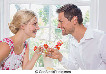 Happy young couple toasting wine glasses - Side view of a...
