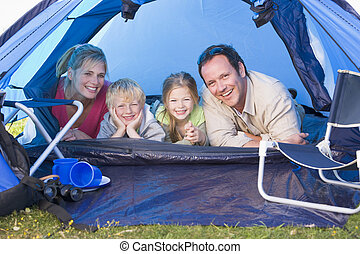 Family camping in tent smiling