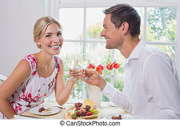 Happy young couple toasting wine gl - Side view portrait of...