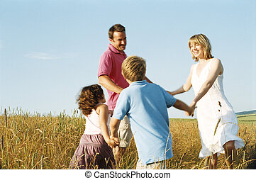 Family playing outdoors smiling