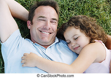 Father and sleeping daughter lying outdoors smiling