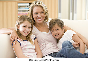 Woman and two young children in living room smiling