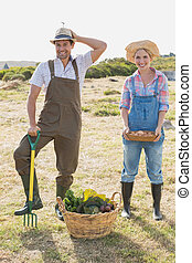 Full length of a smiling couple with vegetables in field