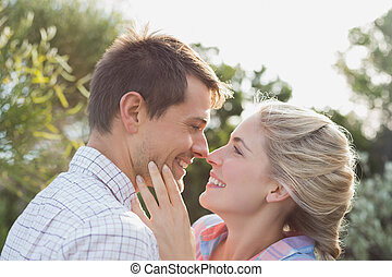 Smiling young couple looking at each other in park