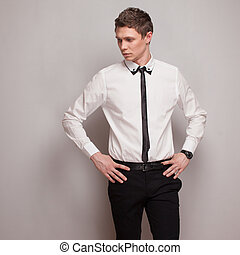 Posing young man model in black and white clothing