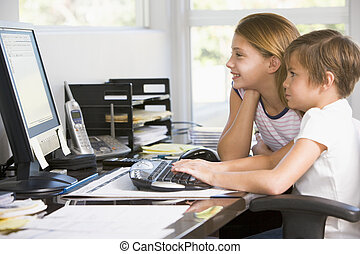 Young boy and young girl in home office with computer...