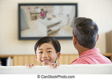 Man and young boy in living room with flat screen television smi