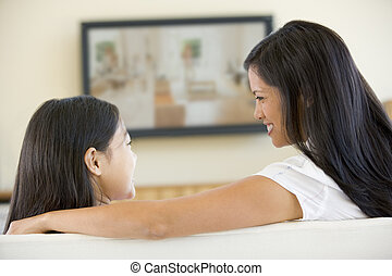 Woman and young girl in living room with flat screen...