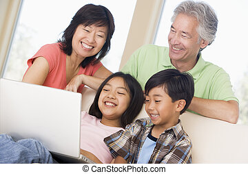 Couple with two young children in living room with laptop smilin