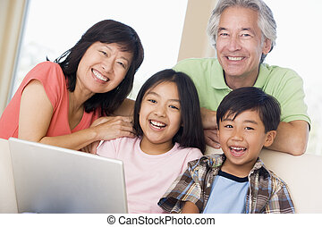 Couple with two young children in living room with laptop...