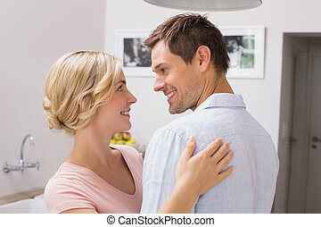 Loving couple looking at each other at home
