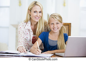 Woman helping young girl with laptop do homework in dining...