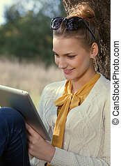 Close Up of using ipad young woman in the park. Touching touchscreen
