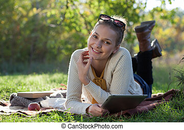 smiling woman lying on bedding with ipad during fun outdoors