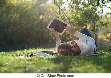 woman lying on bedding on green grass with ipad during...