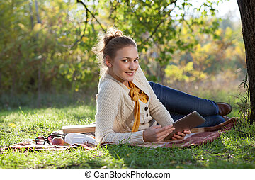 woman lying on bedding on green grass with ipad during rest in the park