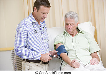 Doctor checking man\\\'s blood pressure in exam room