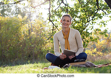woman sitting on bedding on green grass with tablet pc during picknic in the park