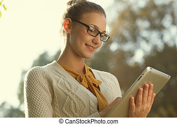 Closeup of young smart woman with tablet outdoors Distance...