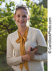 closeup of happy woman in glasses with tablet pc in hands in...