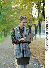 Hipster style young woman using tablet pc in autumn street