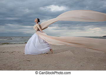 female model in long beige dress posing dynamic in the beach...