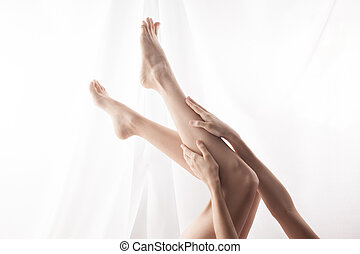 Lying woman stroking feet. high key