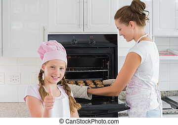 Girl gesturing thumbs up while mother removes cookies from...