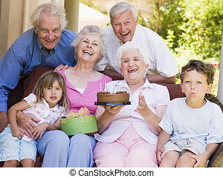 Grandparents and grandchildren on patio with cake and gift...