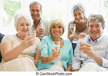 Five friends in living room drinking champagne and smiling