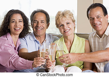 Two couples in living room drinking champagne and smiling