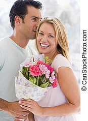 Husband and wife holding flowers and smiling