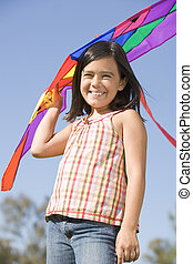 Young girl with kite outdoors smiling
