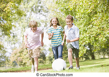 Three young friends playing soccer