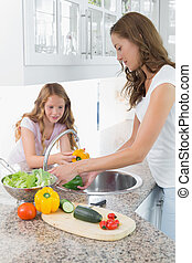 Girl helping her mother to wash vegetables in kitchen -...