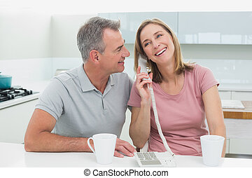 Happy couple using landline phone in kitchen - Happy couple...