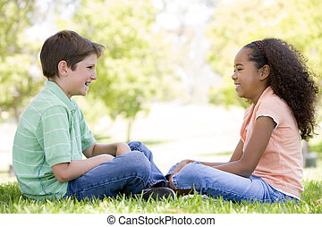 Tow young friends sitting outdoors looking at each other and...