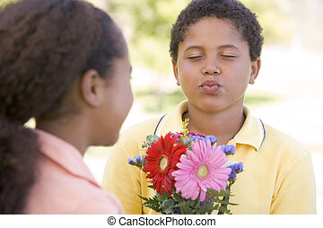 Young boy giving young girl flowers and puckering up