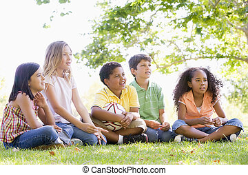 Five young friends sitting outdoors with soccer ball