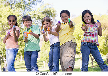 Five young friends with water guns outdoors smiling