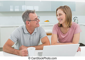 Couple using laptop while man drinking coffee in the kitchen...