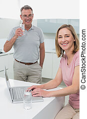 Woman using laptop while man drinking water in kitchen -...