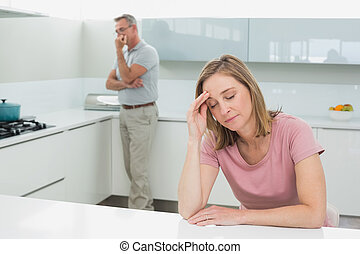 Couple not talking after an argument in kitchen - Unhappy...