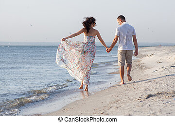 Backview of walking couple among seashore during sunset Girl...