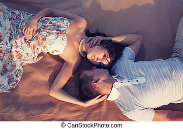 Beautiful couple lying down and kissing on the beach