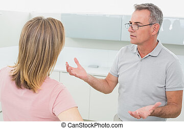 Unhappy couple having an argument in kitchen - Unhappy...
