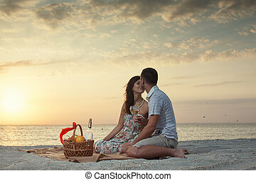 Couple On Beach With Luxury Wine Picnic during beautiful...