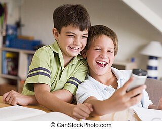 Two Young Boys Distracted From Their Homework, Playing With...