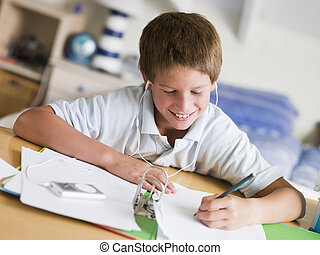 Young Boy Doing His Homework While Listening To Music On His...