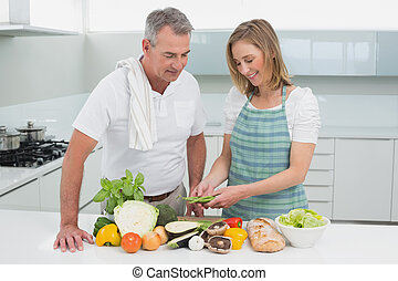 Happy couple preparing food together in kitchen - Portrait...